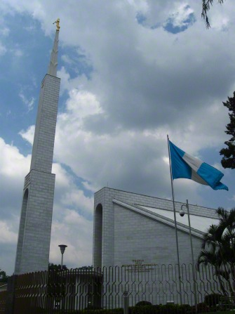 A view of the spire near the Guatemala City Guatemala Temple, with the Guatemalan flag flying in the foreground.