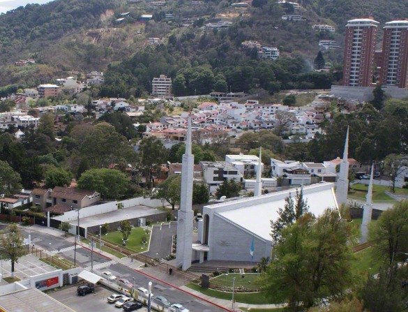 A view from afar of the Guatemala City Guatemala Temple, with the surrounding neighborhoods, buildings, and streets in the frame.