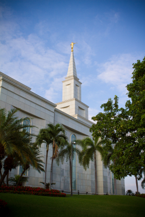 The spire and the angel Moroni on the Guayaquil Ecuador Temple, with a green lawn and palm trees below.