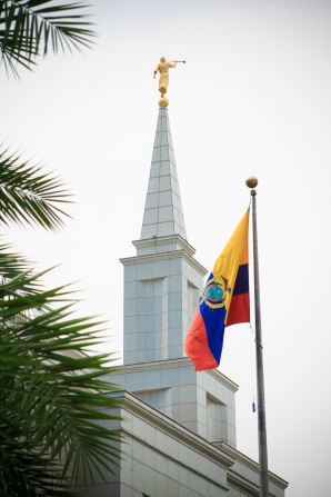 The spire of the Guayaquil Ecuador Temple, with palm leaves on the left side and the Ecuadorian flag on the right in the foreground.