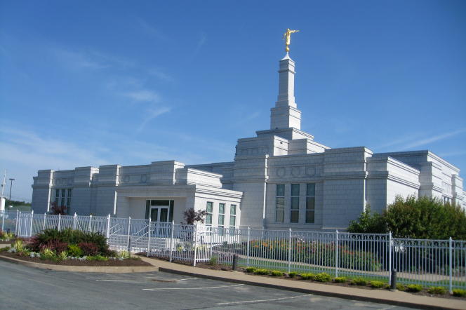 The Halifax Nova Scotia Temple during the daytime, with the grounds enclosed in a white fence.