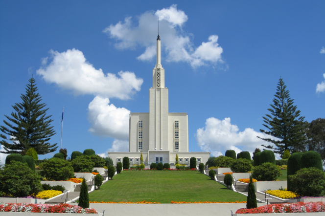 The Hamilton New Zealand Temple on a clear day, with a green lawn and flower beds leading to the entrance.