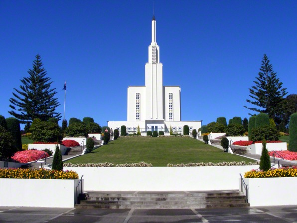 The front of the Hamilton New Zealand Temple, with a green lawn leading toward the doors and interspersed with blooming flower beds.