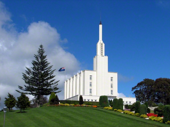 The Hamilton New Zealand Temple, with a neatly manicured green lawn and a thin white cloud in the blue sky to the left of the temple's spire.