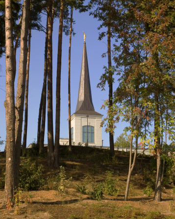 The spire of the Helsinki Finland Temple rising over a hill and seen between a clump of trees on the temple grounds.
