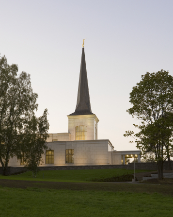 A side view of the spire on the Helsinki Finland Temple, with the lights on in the early evening and two large trees on either side.