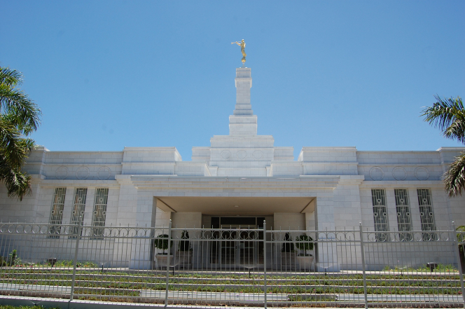 The front entrance to the Hermosillo Sonora Mexico Temple on a clear sunny day, with green trees on either side of the entrance.