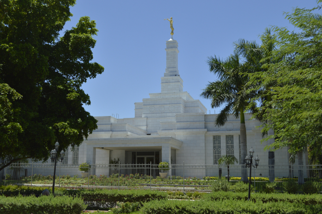 The Hermosillo Sonora Mexico Temple on a sunny day, surrounded by green shrubbery and trees.