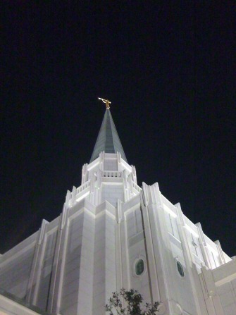 An upward view of the spire and angel Moroni statue on the Houston Texas Temple at night.
