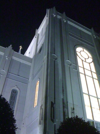A detail view of several windows on the Houston Texas Temple at night, illuminated by the warm lights inside.