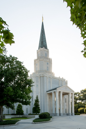 A portrait of the Houston Texas Temple, framed by green leaves on nearby trees, during the daytime.