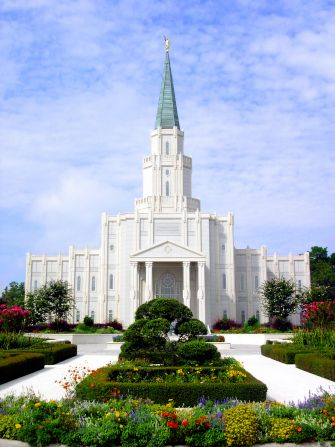 The front of the Houston Texas Temple on a sunny day, with flower beds and green trees forming a median on the path to the doors.