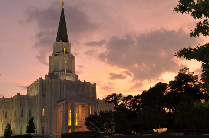 The Houston Texas Temple in the evening, just after sunset, with a purple and pink sky in the background and the shadows of trees over to the right side.
