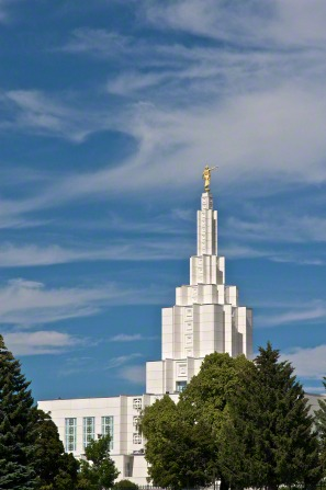 The top half of the Idaho Falls Idaho Temple rising above the trees on a sunny day, with a blue sky in the distance.
