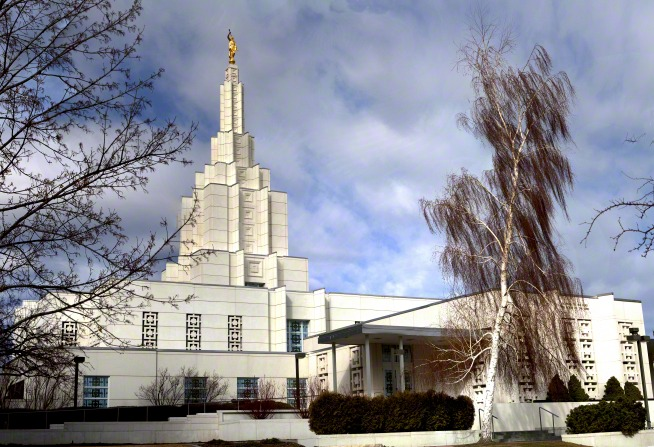 A front side view of the Idaho Falls Idaho Temple on an autumn day, with a tall red tree blowing in the wind.