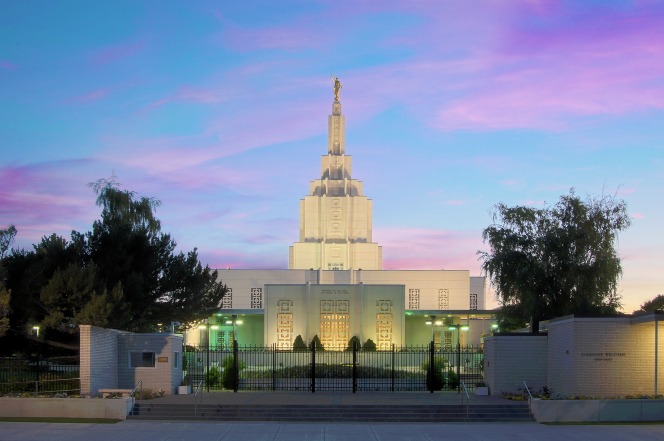 The front of the Idaho Falls Idaho Temple in the evening, illuminated by the temple's lights inside and outside.