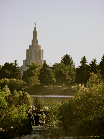 Green scenery seen on a sunny day in front of the Idaho Falls Idaho Temple, which can be seen in the background.