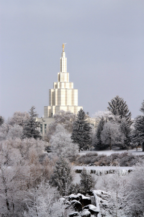 The spire of the Idaho Falls Idaho Temple rising over the snow-covered trees in front of a gray sky on a winter day.