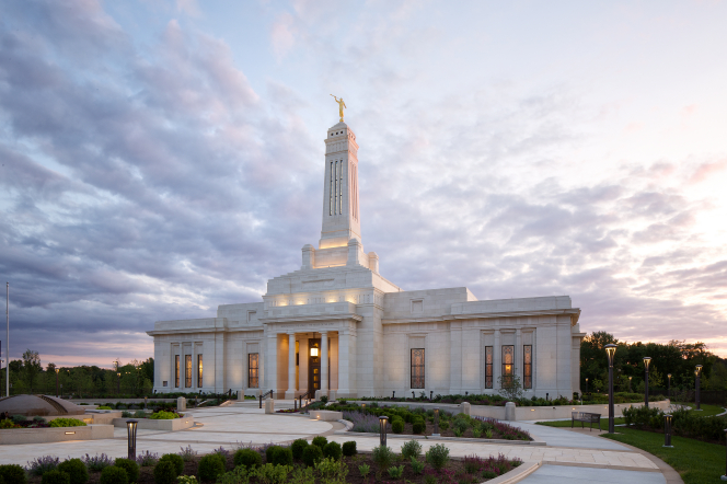 A side view of the Indianapolis Indiana Temple and its surrounding landscape at sunset.