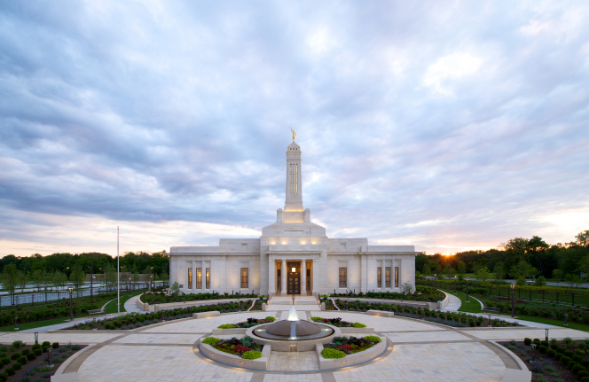 A fountain in front of the Indianapolis Indiana Temple, with clouds and a sunset in the background.