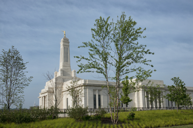 A side view of the Indianapolis Indiana Temple, including grass, trees, and a fence.