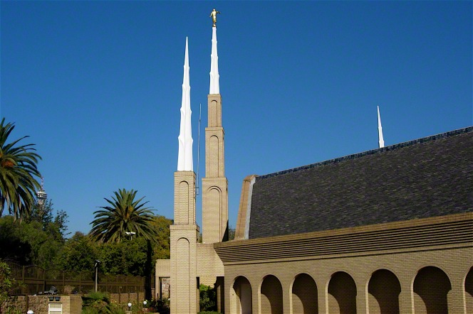 A side front view of the Johannesburg South Africa Temple and spires, with local vegetation seen growing to the side.