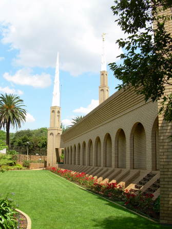 A side view of the Johannesburg South Africa Temple, with green lawns beyond and rows of red flowers growing near the temple walls.