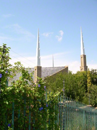 The spires on the Johannesburg South Africa Temple, rising above the green vegetation on the fence surrounding the temple.