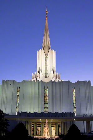 The front of the Jordan River Utah Temple at night, with the lights on inside and outside the temple, illuminating the building and the water fountain in front.