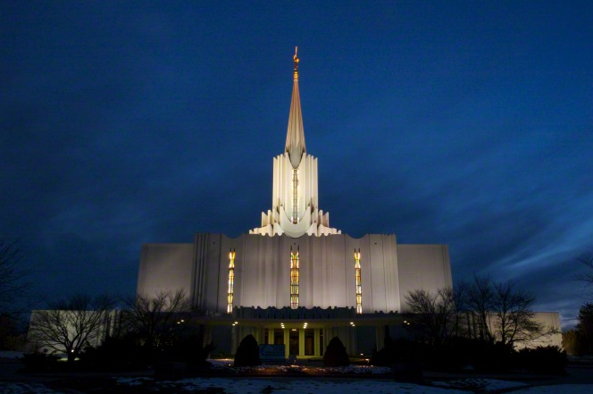 The front of the Jordan River Utah Temple on a winter night, with yellow light shining through the windows and bare trees near the entrance.