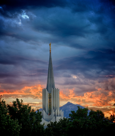 The spire on the Jordan River Utah Temple rising above the nearby trees, in front of a sunset that is showing layers of color in the sky.
