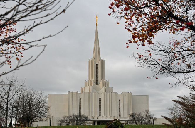 The Jordan River Utah Temple on a gray fall day, with an orange tree to the top right of the frame.