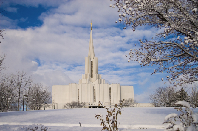 The Jordan River Utah Temple on a winter day, with a bare tree to the right side and a blue sky full of white clouds.