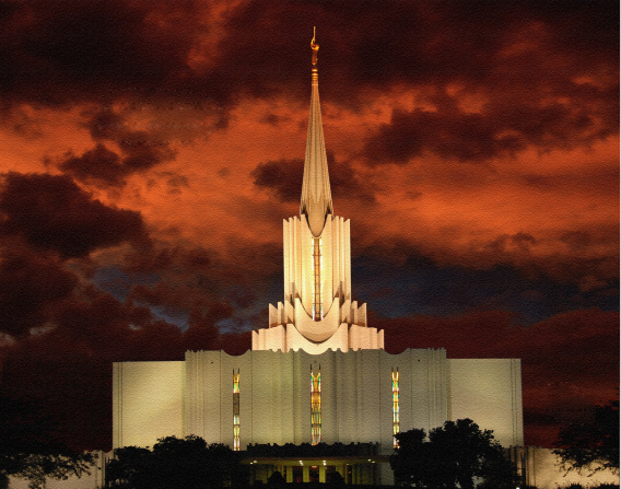 The front of the Jordan River Utah Temple at night, with a deep orange sky in the distance and the temple's windows illuminated by inside light.