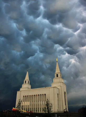 A view of the Kansas City Missouri Temple on a stormy day, looking up past the spires and into the gray clouds above.