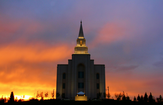 A front view of the Kansas City Missouri Temple at sunset, with orange and red colors in the sky and the lights on the temple illuminating the stone.