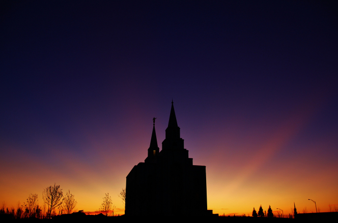 A silhouetted image of the Kansas City Missouri Temple, with the orange and purple colors of the sunset in the background.