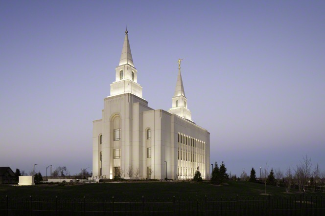 The Kansas City Missouri Temple at night, with the lights illuminating the exterior of the building and a blue sky above.