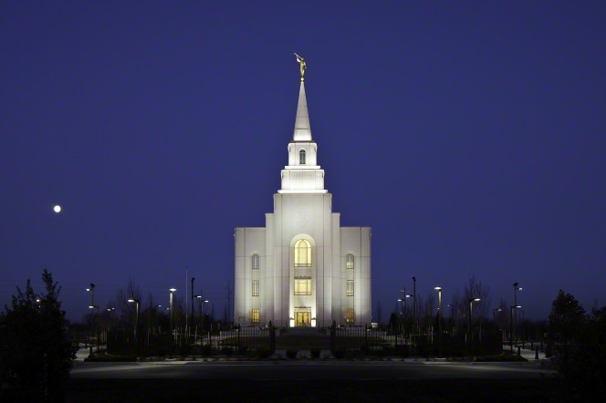 A front portrait view of the Kansas City Missouri Temple at night, illuminated by exterior lights.