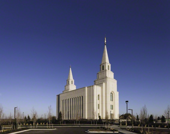 A view of the front and side of the Kansas City Missouri Temple in the daytime, with small trees growing around the parking lot.