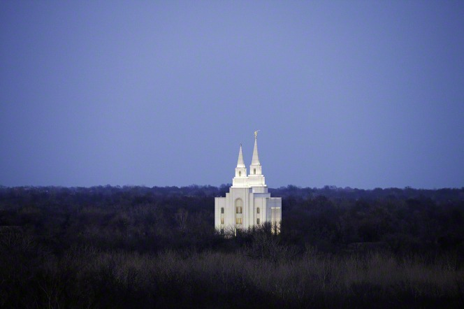 A view of the Kansas City Missouri Temple rising above bare trees in the foreground, with the lights on in the evening.