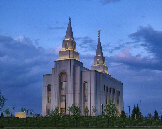 The Kansas City Missouri Temple, with the lights on in the evening and the green lawns surrounded by a black fence.