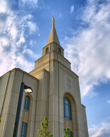 The front spire with the angel Moroni on the Kansas City Missouri Temple, with white clouds in a bright blue sky.