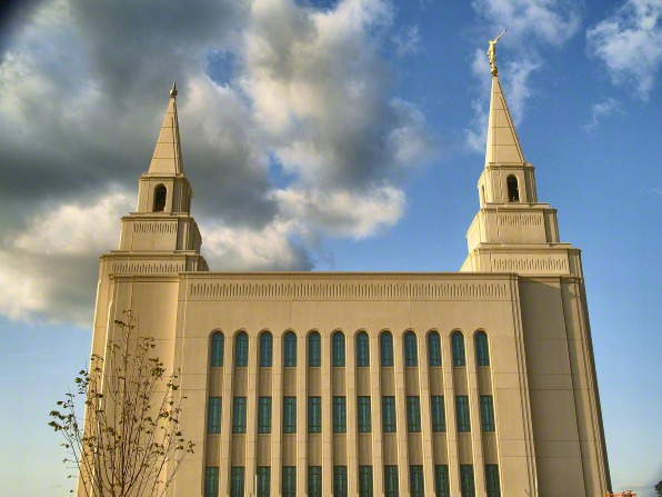 A side view of the Kansas City Missouri Temple, with a small tree in the foreground and a large cloud on the left side.
