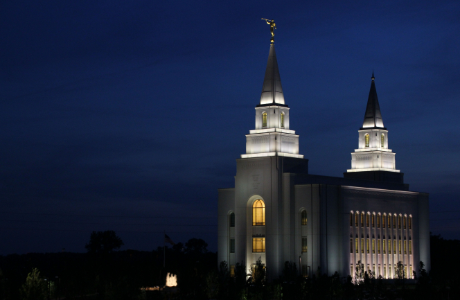 A front view of the Kansas City Missouri Temple at night, illuminated by the lights outside and inside the temple, with a dark sky in the background.