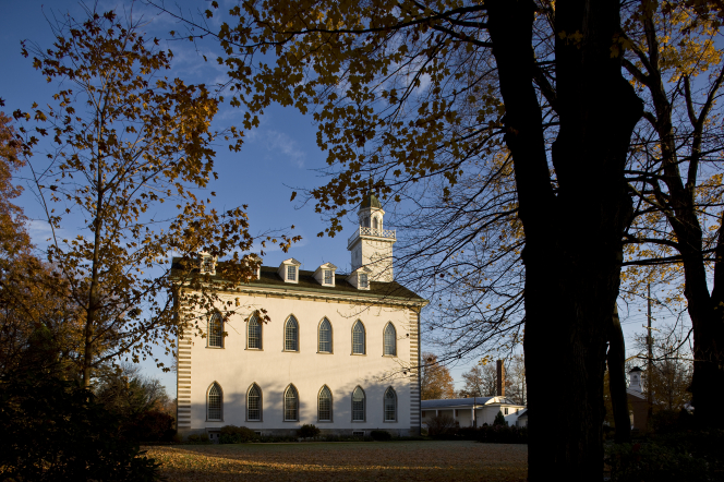 A view of the Kirtland Temple on an autumn day, with the trunk of a large tree partially blocking the view.