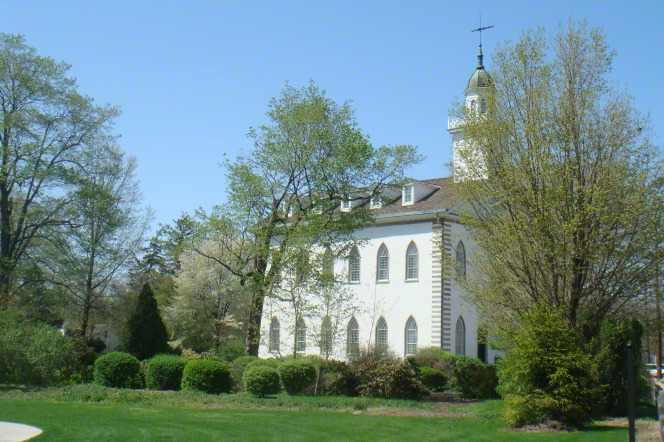 The Kirtland Temple on a bright cloudless day, with large green trees partially blocking the view of the temple.