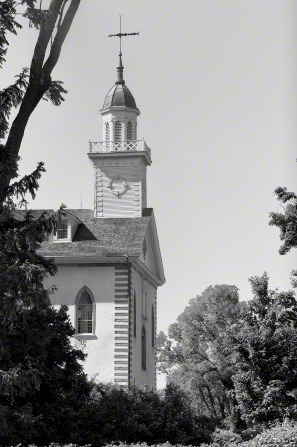 A black and white side view of the front half of the Kirtland Temple, with the branches of a tree on the left-hand side.