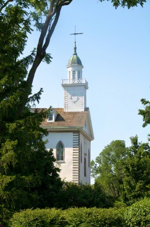 A side view of the front half of the Kirtland Temple, with the branches of a tree on the left-hand side.