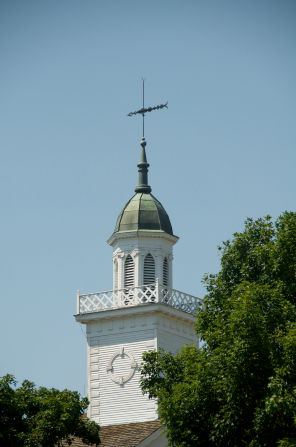 A detail of the spire on the Kirtland Temple, with the green leaves of several trees in view near the bottom of the frame.